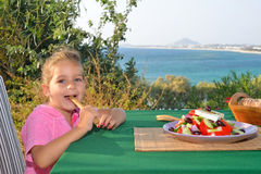 Toddler girl eating tradiotional Mediterranean salad Royalty Free Stock Photos