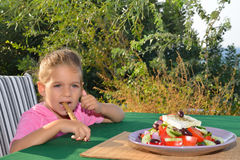 Toddler girl eating tradiotional Mediterranean salad Royalty Free Stock Photography