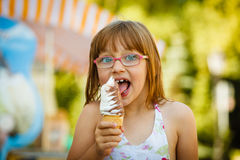 Toddler girl in eyeglasses eating ice cream Royalty Free Stock Images