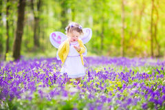Toddler girl in fairy costume in bluebell forest. Adorable toddler girl with curly hair wearing a fairy costume with purple wings and yellow dress is playing in Stock Photo