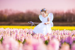 Toddler girl in fairy costume playing in a flower field Royalty Free Stock Image