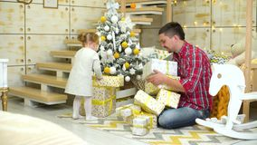 Toddler girl with father put gift boxes under decorated Christmas tree at home stock video footage