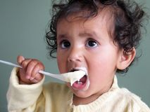 Toddler girl feeding herself with a spoon of porridge. Stock Images