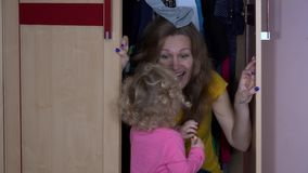 Toddler girl find her mother in closet. Happy child play with mom stock video footage