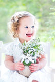Toddler girl with first spring flowers in crystal vase royalty free stock photography