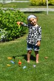 Toddler girl `fishing` on the sunlit summer lawn stock photo