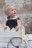 Toddler girl gazing. Blond toddler girl gazing to the right in a wooden cart with a vintage wallpaper background royalty free stock images