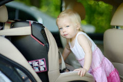 Toddler girl getting into a car seat Royalty Free Stock Images