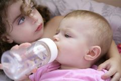 Toddler girl giving bottle of milk to baby sister Stock Images