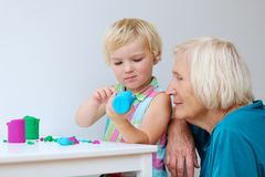 Toddler girl with grandmother creating from plasticine Stock Image