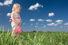 Toddler girl on green meadow stock photos