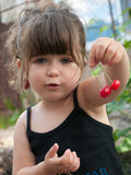 Toddler girl hanging pair of cherries on her ear Stock Photos