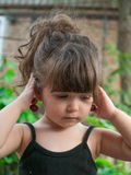 Toddler girl hanging pair of cherries on her ear Stock Photography
