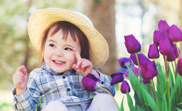 Toddler girl in a hat playing with tulips Stock Photo
