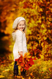 Toddler girl have fun with fallen golden leaves Stock Photo