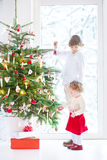 Toddler girl helping her brother to decorate Christmas tree Royalty Free Stock Photos
