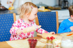 Toddler girl helping at kitchen Stock Image
