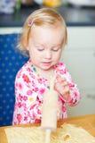 Toddler girl helping at kitchen Royalty Free Stock Image