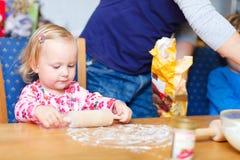 Toddler girl helping at kitchen Royalty Free Stock Photos