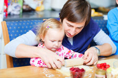 Toddler girl and her dad baking pie Stock Photography