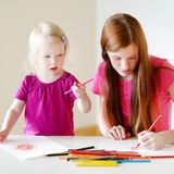Toddler girl and her mom drawing with pencils Stock Image