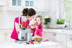 Toddler girl and her mother making fresh strawberry Stock Photos