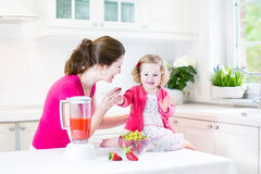 Toddler girl and her mother making fresh strawberry Stock Image