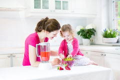 Toddler girl and her mother making fresh strawberry Royalty Free Stock Photos