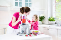 Toddler girl and her mother making fresh strawberry Stock Images
