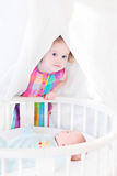 Toddler girl hiding from her newborn baby brother Royalty Free Stock Images