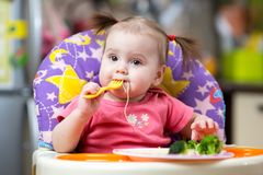 Toddler girl in a highchair for feeding with fork Royalty Free Stock Image