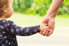 Toddler girl holding hands with her father Royalty Free Stock Photos