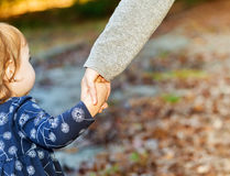 Toddler girl holding hands with her mother on a fall day Royalty Free Stock Photography