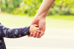 Toddler girl holding hands with her parent Royalty Free Stock Images
