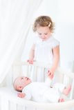 Toddler girl holding hands with newborn brother Stock Photo