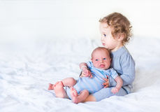 Toddler girl holding her newborn baby brother Stock Photos