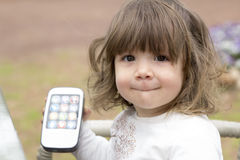 Toddler girl holding toy telephone in hand Royalty Free Stock Images