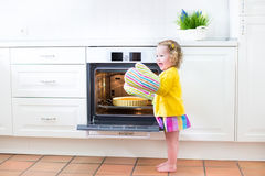 Toddler girl in kitchen mittens next to oven with apple pie Royalty Free Stock Photo