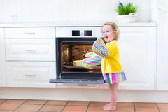 Toddler girl in kitchen mittens next to oven with apple pie Stock Photo