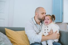 The toddler girl cries in her father`s arms. royalty free stock photo