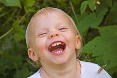 Toddler Girl Laughing With Food in Her Mouth Royalty Free Stock Photography