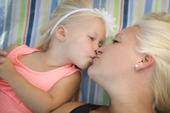 Toddler Girl Laying on Blanket Kisses Her Mommy Stock Photos