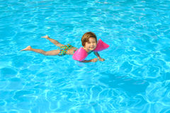 Toddler girl learning to swimm in the swimming pool Stock Photography