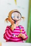 Toddler girl looking through magnifier Royalty Free Stock Photos