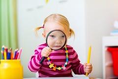 Toddler girl looking through magnifier Royalty Free Stock Image