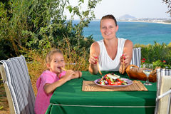 Toddler girl lunching tradiotional Mediterranean salad with her Stock Photo