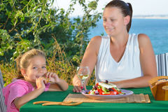 Toddler girl lunching tradiotional Mediterranean salad with her Stock Image