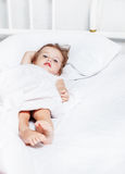 Toddler girl lying in bed Stock Photo