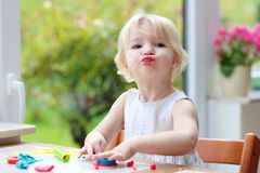 Toddler girl making cookies from plasticine Royalty Free Stock Photos