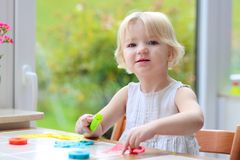 Toddler girl making cookies from plasticine Stock Photo